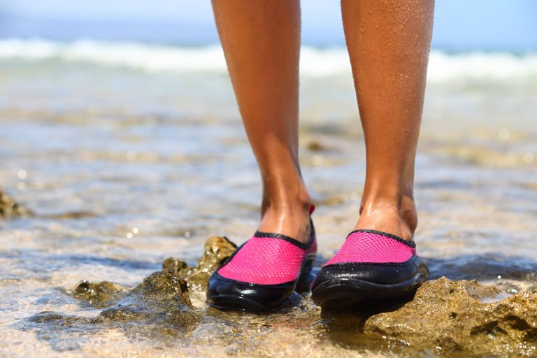 Bottom of woman's legs wearing pink water shoes on a rocky beach